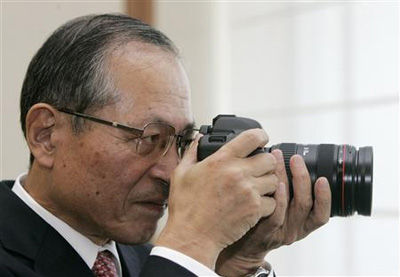 Canon Inc. President Tsuneji Uchida looks through the viewfinder of a 5D Mark II trying to take a picture of falling Canon market share numbers. I hope he had it configured in AI-Servo mode. I bet the 9 point AF really wasn't enough either.